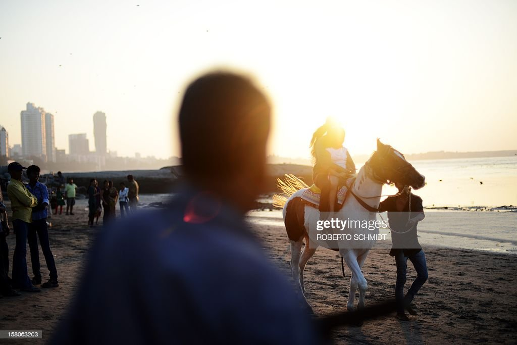 An Indian man gives beach goers a ride on his horse for a small sum on a beach in Mumbai on December 10, 2012. AFP PHOTO/Roberto Schmidt