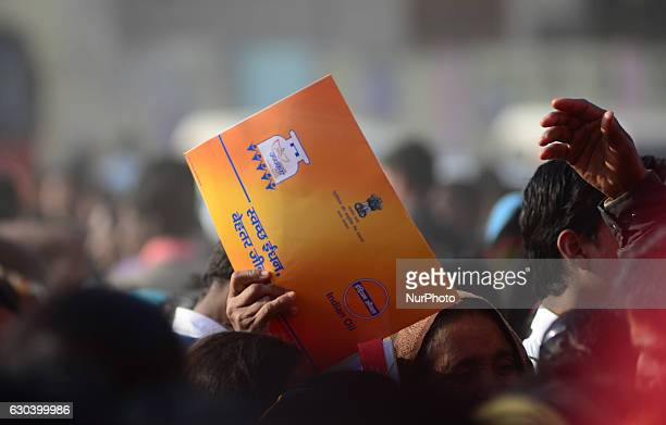 An indian man holding a free gas connection card stand in Queue to get lunch packet given by Minister of state for Patrolium and natural gas Mr...