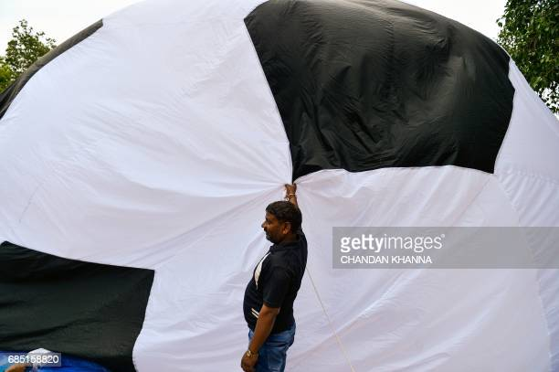 An Indian man holds a balloon in the shape of a football is installed during the kick off function for the FIFA U17 World Cup in New Delhi on May 19...
