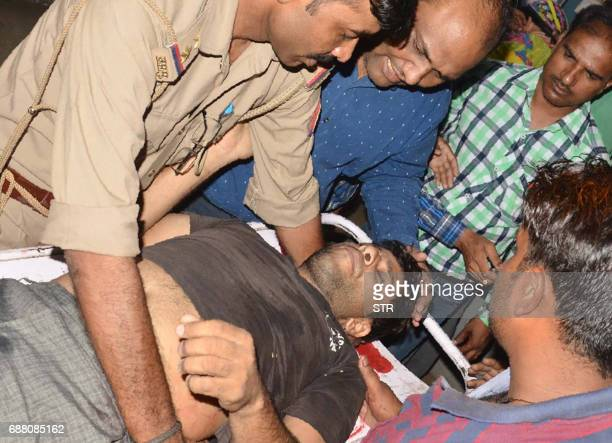 An Indian man injured in clashes between different castes is brought to hospital in the Saharanpur district in the state of Uttar Pradesh on May 24...