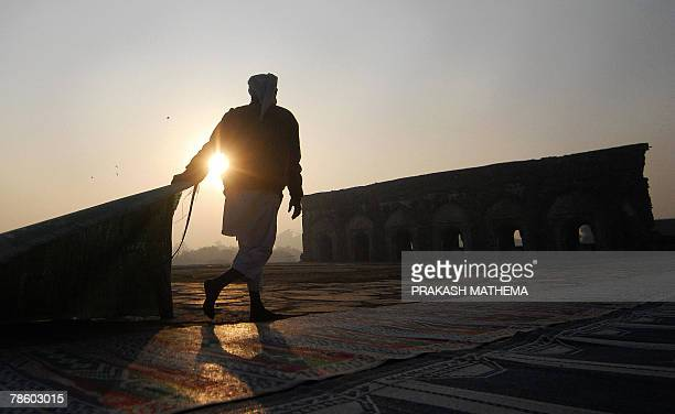 An Indian man lays carpets on the ground of the Feroz Shah Kotla Mosque ahead of prayers in New Delhi 21 December 2007 on the occasion of the Muslim...