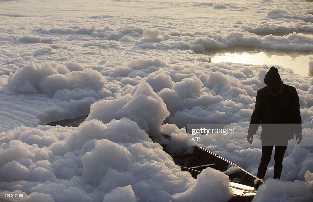 An Indian man looks down at his boat that is covered in polluted foam in the Yamuna river in New Delhi on December 9, 2012. India's Supreme Court said on December 8, all parameters of water quality of river Yamuna indicate that it resembles a drain and urged authorities to make it pollution-free. Over 2,400 million liters of untreated sewage flows into the Yamuna every day. AFP PHOTO/ Andrew Caballero-Reynolds