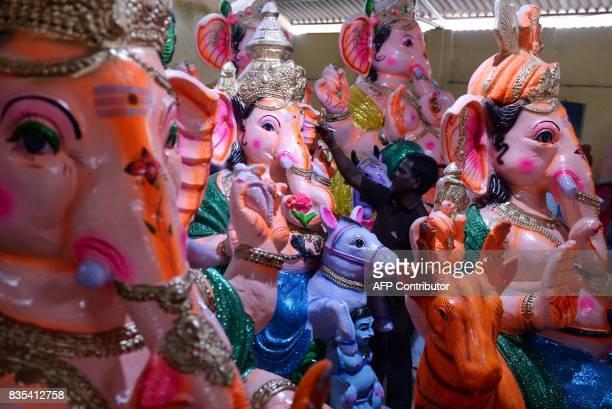 An Indian man marks a finished idol of the elephantheaded Hindu deity Ganesha at a workshop ahead of the Ganesh Chaturthi festival in Chennai on...