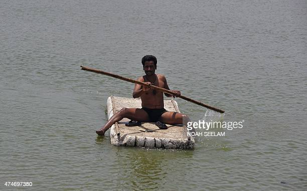 An Indian man paddles himself in the water on the outskirts of Hyderabad on May 25 2015 More than 430 people have died in two Indian states from a...