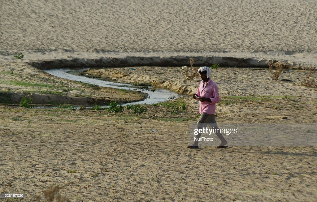 An indian man passes through a dried and shrinked sub stream of Yamuna River , during a hot day in Allahabad on May 4,2016.