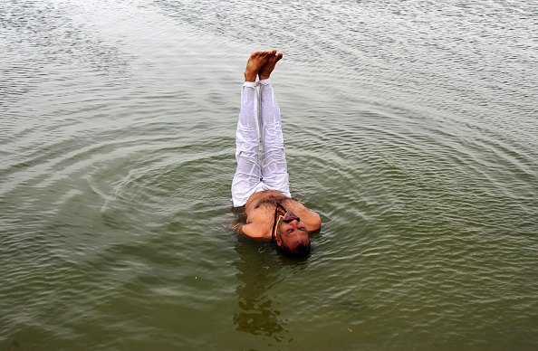 An Indian man performing yoga in Water of River Yamuna on the eve of International Yoga day in Allahabad