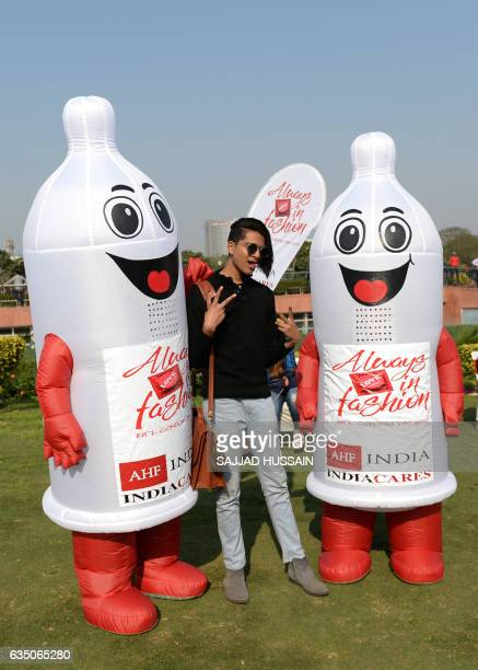 An Indian man poses with volunteers wearing condom during an event to mark International Condom Day in New Delhi on February 13 2017 The event was...