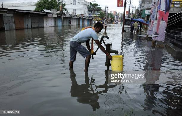 An Indian man pumps water on a flooded street after heavy rain brought by Cyclone Mora in Agartala the capital of northeastern state of Tripura on...