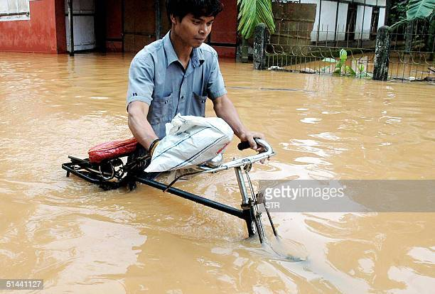 An Indian man pushes his bicycle through flood waters 08 October 2004 in the capital city of India's eastern state of Assam Guwahati At least 38...