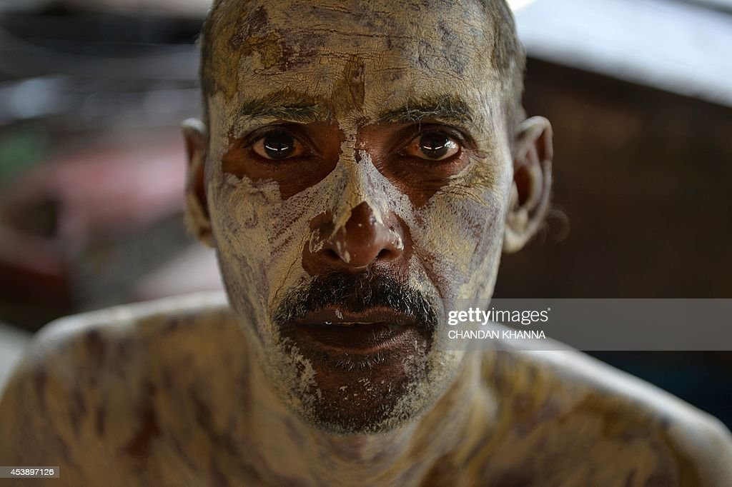 An Indian man puts 'fullers earth' on his body as a cure for skin disease caused by mosquito bites, in New Delhi on August 21, 2014. Fullers earth, a clay substance that is hugely popular for its healing property against acne and blemishes, is very rich in magnesium chloride which helps to reduce acne. Originally used as an absorbent in the wool industry this ingredient is now greatly used in many skin care products. AFP PHOTO/ Chandan KHANNA