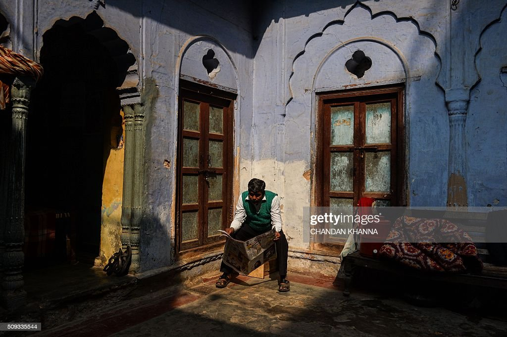 An Indian man reads a newspaper as he sits in the corner of a courtyard at a community guesthouse in the old quarters of New Delhi on February 10, 2016. AFP PHOTO / Chandan KHANNA / AFP / Chandan Khanna
