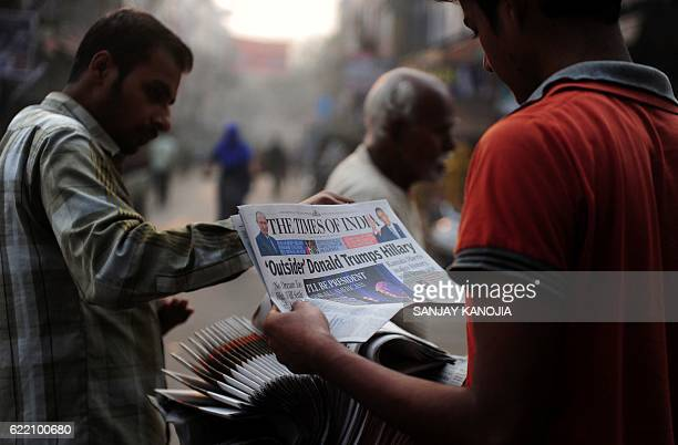 An Indian man reads a newspaper carrying reports of the newly elected US President Donald Trump on a street in Allahabad on November 10 2016 Indian...