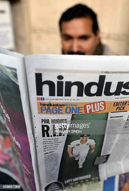 An Indian man reads a newspaper regarding the death of Australian batsman Phillip Hughes in Sydney the day before in New Delhi on November 28 2014...