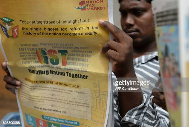 An Indian man reads up abuot the new Goods and Services Tax at a shop in Chennai on June 30 2017 India is bracing for its most significant reform in...