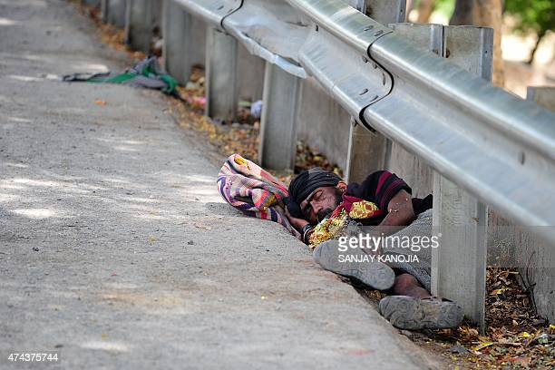 An Indian man rests on the road side during a hot summer day in Allahabad on May 22 2015 AFP PHOTO/ SANJAY KANOJIA