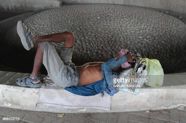 An Indian man rests under a railway bridge on a hot summer day in Allahabad on April 14 2017 / AFP PHOTO / SANJAY KANOJIA