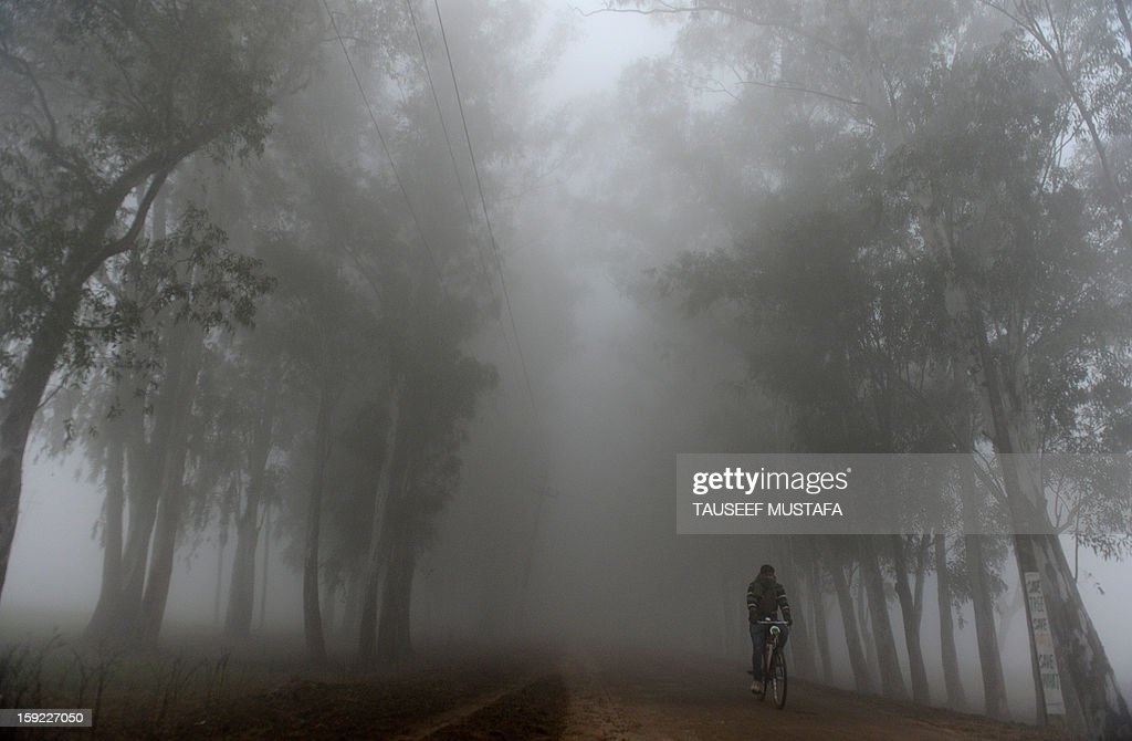 An Indian man rides his bicycle during a dense fog along the India-Pakistan border in Suchit-Garh, 36 kms southwest of Jammu on January 10, 2013. The beheading of an Indian soldier may have sparked a war of words between Delhi and Islamabad but the two nuclear rivals are both determined to prevent it from wrecking a fragile peace process. Two Indian soldiers died after a firefight erupted in disputed Kashmir on Tuesday as a patrol moving in fog discovered Pakistani troops about 500 metres (yards) inside Indian territory, according to the Indian army. AFP PHOTO/Tauseef MUSTAFA