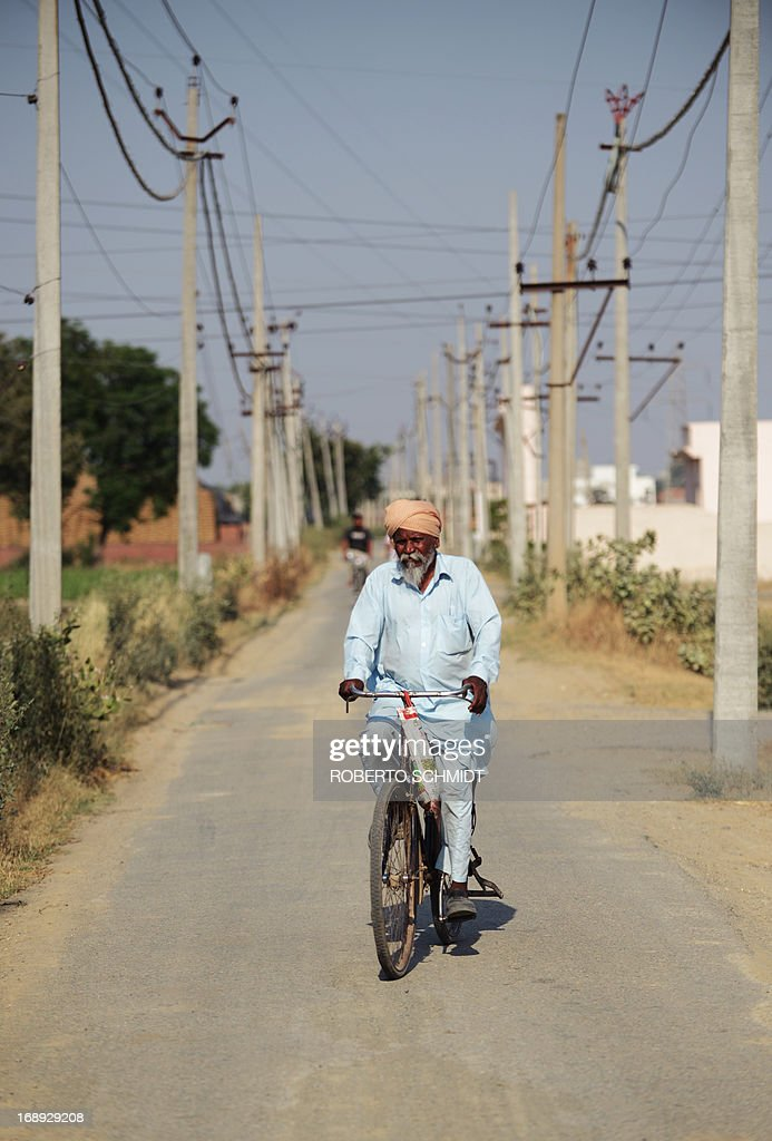 An Indian man rides his bicycle near electricity lines in a street near an electricity sub station in the northwestern Indian city of Amritsar on May 16, 2013. India, which has one of the largest integrated electricity grids in the world is challenged by peak electricity demands from consumers in the summer months of June and July when the temperatures hover at around 48 Degrees Celcius. AFP PHOTO/ROBERTO SCHMIDT