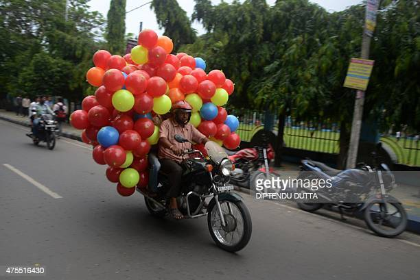 An Indian man rides his motorcycle loaded with plastic balls in Siliguri on June 1 2015 India reported economic growth of 73 percent for 201415 up...