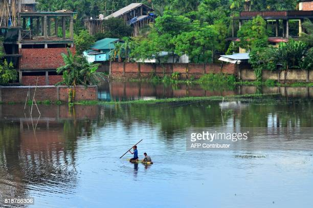TOPSHOT An Indian man rows a makeshift raft through a flooded area at Mao Colony in Dimapur in Nagaland state on July 19 2017 / AFP PHOTO / Caisii Mao