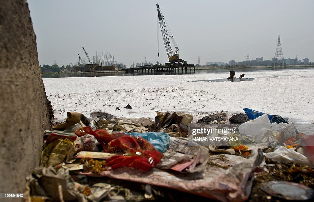 An Indian man searches for coins in the polluted waters of the Yamuna river in New Delhi on June 4, 2013 on the eve of World Environment Day. India's cities are becoming more polluted and unhealthy, according to a new survey published Monday showing growing concern about the impact of high economic growth on the environment. The Energy and Resources Institute (TERI) research group based in New Delhi questioned 4,039 people living in India's six biggest cities about their perceptions, opinions and awareness of the environment and green issues over the last five years.