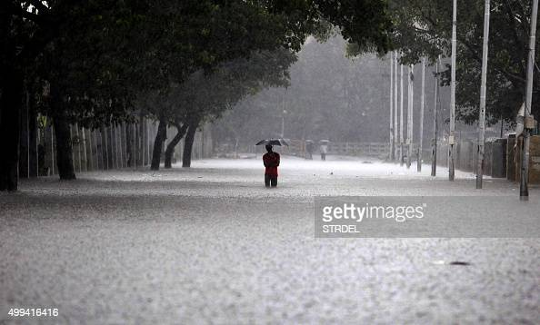 TOPSHOT An Indian man shelters under an umbrella as he walks through floodwaters in Chennai on December 1 during a downpour of heavy rain in the...