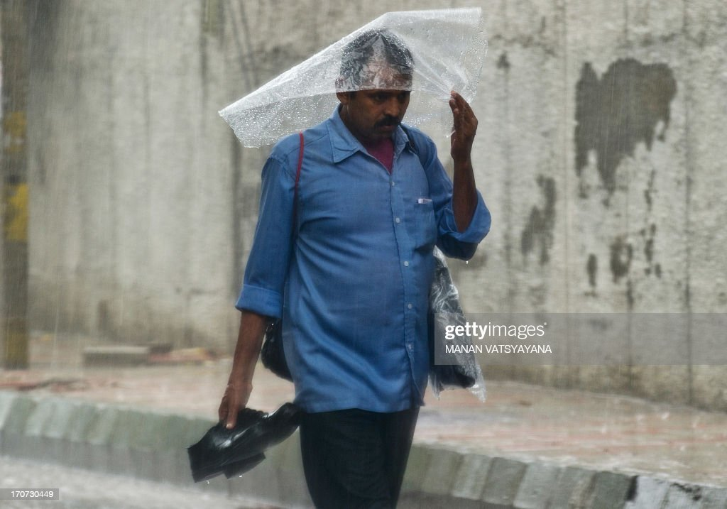 An Indian man shields himself with a plastic sheet and carries his shoes in his hand during a heavy downpour in New Delhi on June 17, 2013. According the India Meteorological Department (IMD) , Indias monsoon, which accounts for more than 70 percent of the annual rainfall, may be the highest in two years, potentially boosting harvests of everything from rice to corn, sugar cane and cotton. The IMD reported that rainfall will be 98 percent of the 50-year average of 89 centimetres (35 inches) in the four months through September. AFP PHOTO/ MANAN VATSYAYANA