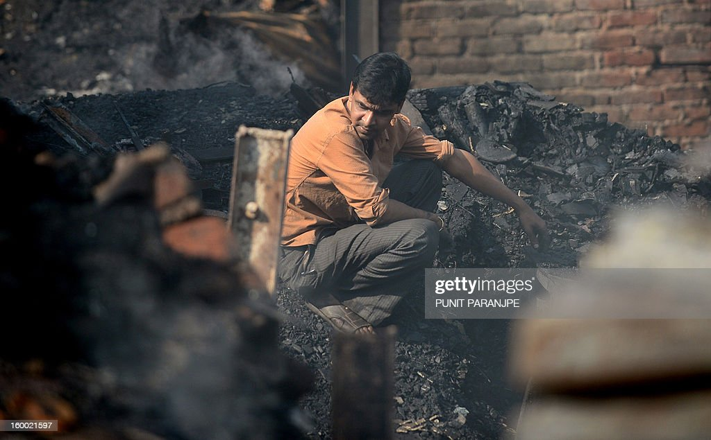 An Indian man sits amidst the debris after a fire raged through the Nayanagar slum in Mumbai on January 25, 2013. A fire killed six people when it ripped through a slum in the heart of Mumbai on January 25 and left hundreds homeless, emergency services said.