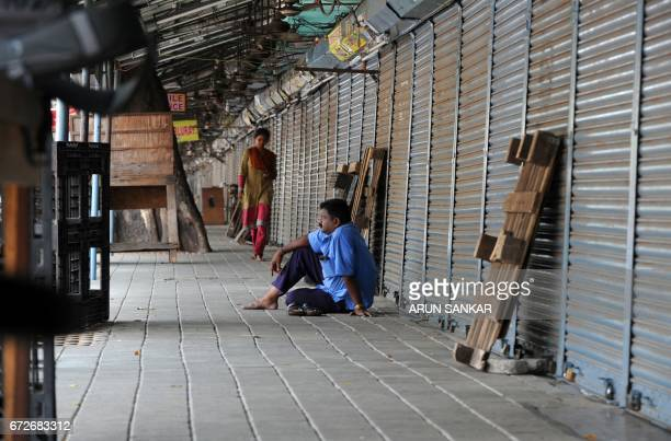 An Indian man sits next to shuttered stores during a statewide strike in support of farmers in Chennai on April 25 2017 Tamil Nadu state farmers are...