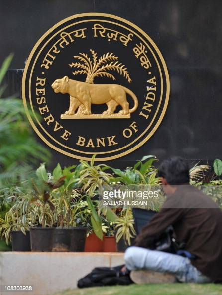 An Indian man sits outside the Reserve Bank of India building in Mumbai on January 25 2011 India on January 25 hiked interest rates to their highest...