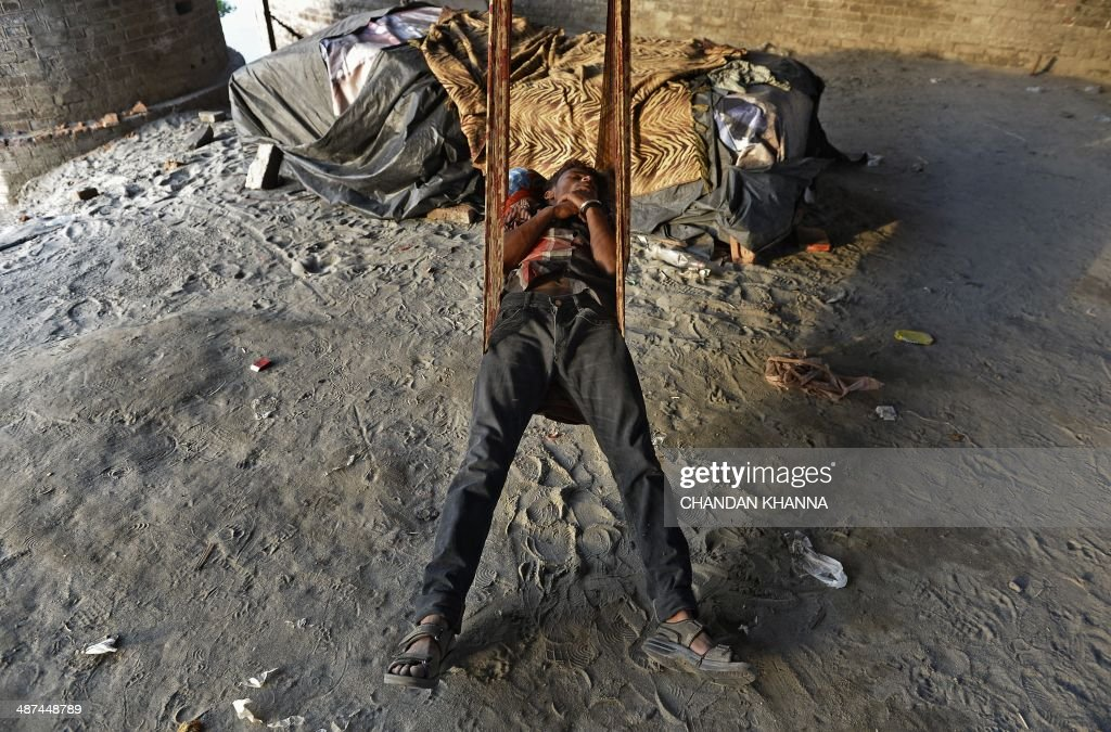 An Indian man sleeps on a swing made of a sari under the bridge on the banks of river Yamuna in New Delhi on April 30, 2014. Delhi is producing 1,900 million liter per day (MLD) of sewage but Delhi Jal Board (DJB) responsible for managing sewage is collecting and treating only 54 per cent of the total sewage generated in the city. AFP PHOTO/Chandan KHANNA