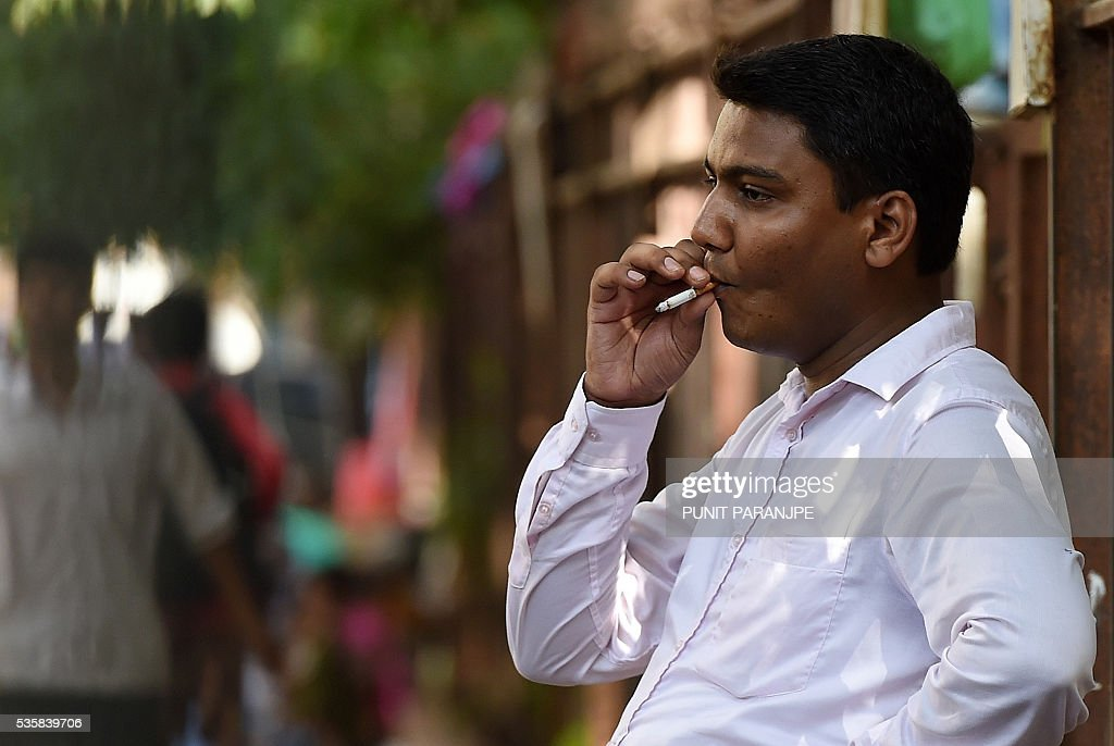 An Indian man smokes a cigarette near the street side shop on the eve of 'World No Tobacco Day' in Mumbai on May 30, 2016. Many countries are considering following the example of Australia and introducing 'plain packaging' of cigarettes with graphic health warnings which are said to reduce the appeal of smoking. / AFP / PUNIT