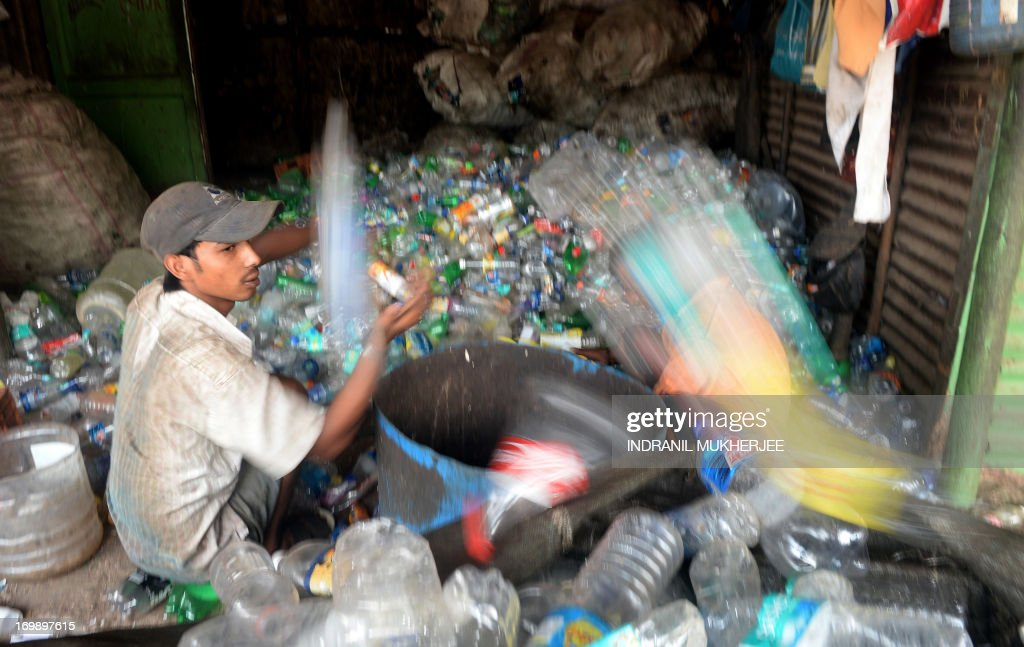 An Indian man sorts used plastic bottles for recycling at a roadside unit in Mumbai on June 4, 2013 on the eve of World Environment Day. India's cities are becoming more polluted and unhealthy, according to a new survey published Monday showing growing concern about the impact of high economic growth on the environment. The Energy and Resources Institute (TERI) research group based in New Delhi questioned 4,039 people living in India's six biggest cities about their perceptions, opinions and awareness of the environment and green issues over the last five years. AFP PHOTO/ Indranil MUKHERJEE
