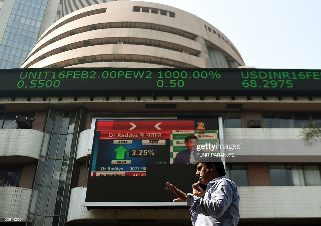 An Indian man speaks on a phone as he walks by stock prices on a digital broadcast on the facade of the Bombay Stock Exchange (BSE) building in Mumbai on February 9, 2016. Asian stocks plunged across the board on February 9, the dollar dived against the yen, gold jumped and yields on Japanese government bonds fell to zero as fears about the global economy sent investors scrambling to safety. AFP PHOTO / PUNIT PARANJPE / AFP / PUNIT PARANJPE