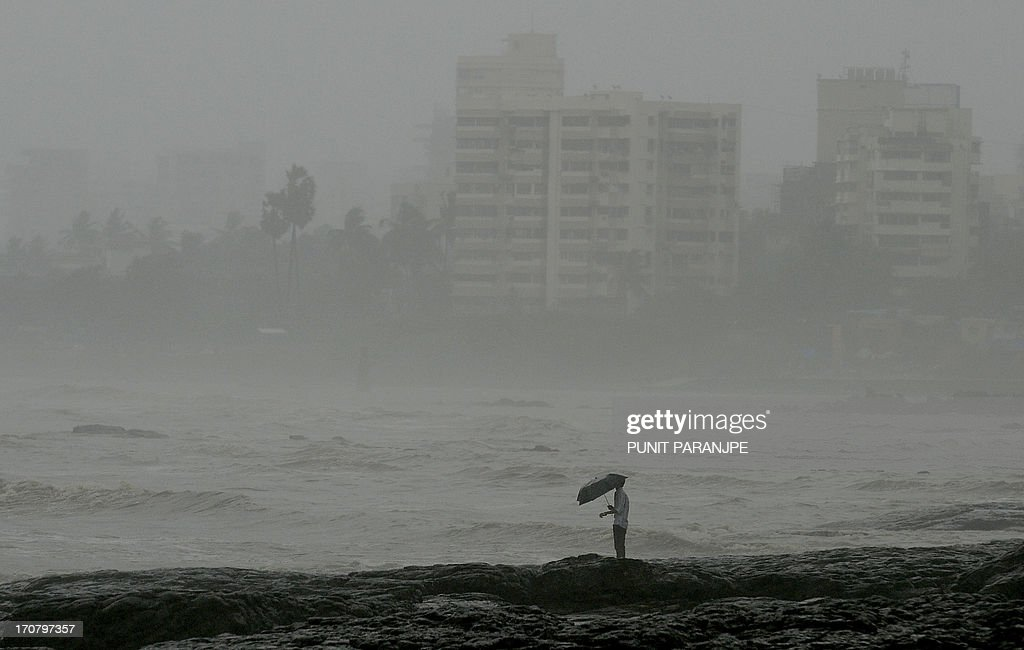 An Indian man stands by the sea front during heavy rain showers in Mumbai on June 18, 2013. The monsoon, which India's farming sector depends on, covers the subcontinent from June to September, usually bringing some flooding. But the heavy rains arrived early this year, catching many by surprise. The country has received 68 percent more rain than normal for this time of year, data from the India Meteorological Department shows.