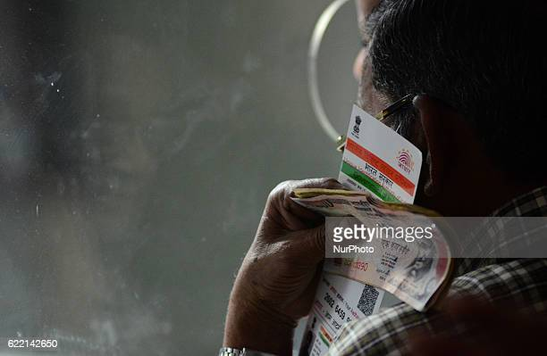 An indian man stands in a queue carring 1000 rupee notes and Aadhar card as he waits his turn to exchange his currency with 100 rupee notes in a bank...