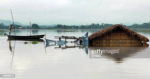 An Indian man steers his country boat through flood water near a submerged house in the floodaffected village of Kukurmara in Kamrup district some 45...