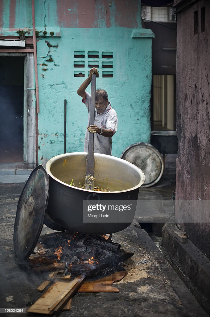 An Indian man stirs an enormous pot of curry in a makeshift outdoor kitchen in Melaka in preparation for a traditional wedding