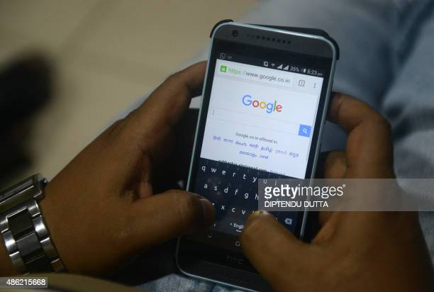 An Indian man surfs on his mobile phone using the Google search engine with its new logo in Siliguri on September 22015 Google refreshed its logo to...