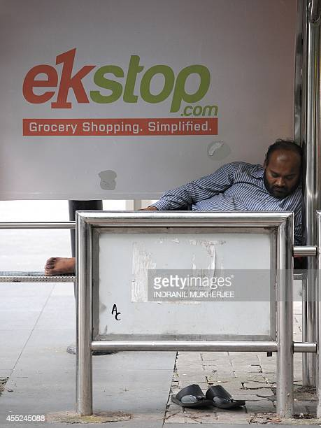 An Indian man takes a nap at a bus stop with a billboard advertisement for an online grocery shopping portal in Mumbai on September 11 2014 India's...