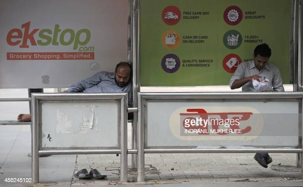 An Indian man takes a nap while another eats a snack at a bus stop with a billboard advertisement for an online grocery shopping portal in Mumbai on...