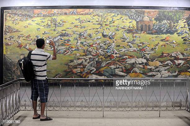 An Indian man takes a photograph of a painting depicting the Jallianwala Bagh massacre in Amritsar on April 12 2011 The Amritsar massacre also known...