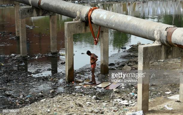 TOPSHOT An Indian man takes a shower as water leaks from a pipeline in New Delhi on June 6 2017 Temperatures are hovering around 45 degrees Celsius...