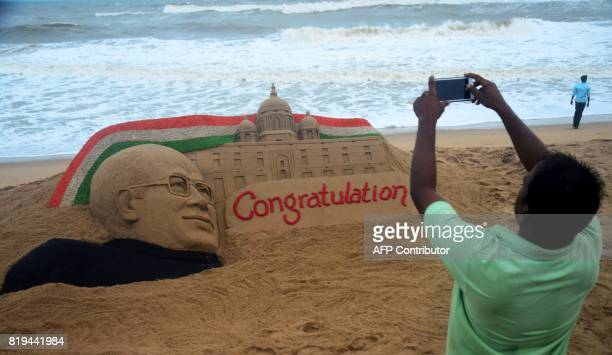 An Indian man takes picture of a sand sculpture by artist Sudarsan Pattnaik depicting Indias President elect Ram Nath Kovind at a beach Puri some 65...