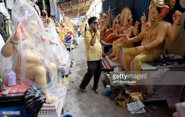 An Indian man talks on his mobile phone standing in front of idols of the elephantheaded Hindu deity Ganesha at a workshop ahead of the Ganesh...