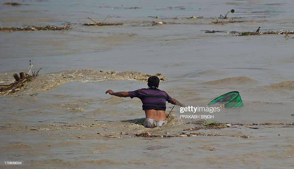An Indian man tries to catch an oil container being carried away in the rising waters of the Yamuna river in New Delhi on June 19, 2013. The monsoon, which India's farming sector depends on, covers the subcontinent from June to September, usually bringing some flooding. But the heavy rains arrived early this year, catching many by surprise and exposing the country's lack of preparedness. Military helicopters dropped emergency supplies to thousands of tourists and pilgrims stranded by flash floods that tore through towns and temples in northern India, killing at least 120 people, officials said. AFP PHOTO/ Prakash SINGH