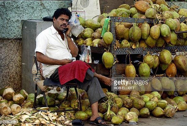An Indian man uses a phone landline as he sits in amongst coconuts on a street in Bombay 15 November 2003 Space on footpaths in the city is at a...