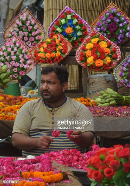 An Indian man Vijay 45 strings rose flowers together to make garlands at a market in Armitsar India's economic growth slowed to 71 percent for the...