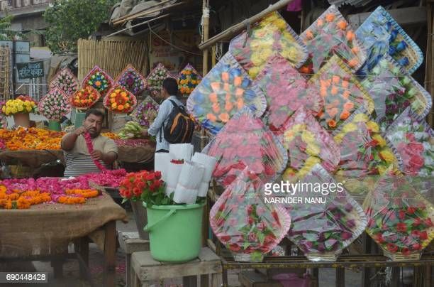An Indian man Vijay 45 strings rose flowers together to make garlands at a market in Amritsar on May 312017 India's economic growth slowed to 71...