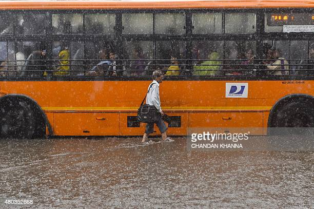 An Indian man walks in the floodwaters on a street in New Delhi on July 11 as the Indian capital experienced heavy monsoon rainfall AFP PHOTO /...